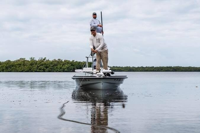 The Naples fishing guide polig his boat on the flats with an angler on the bow of the boat